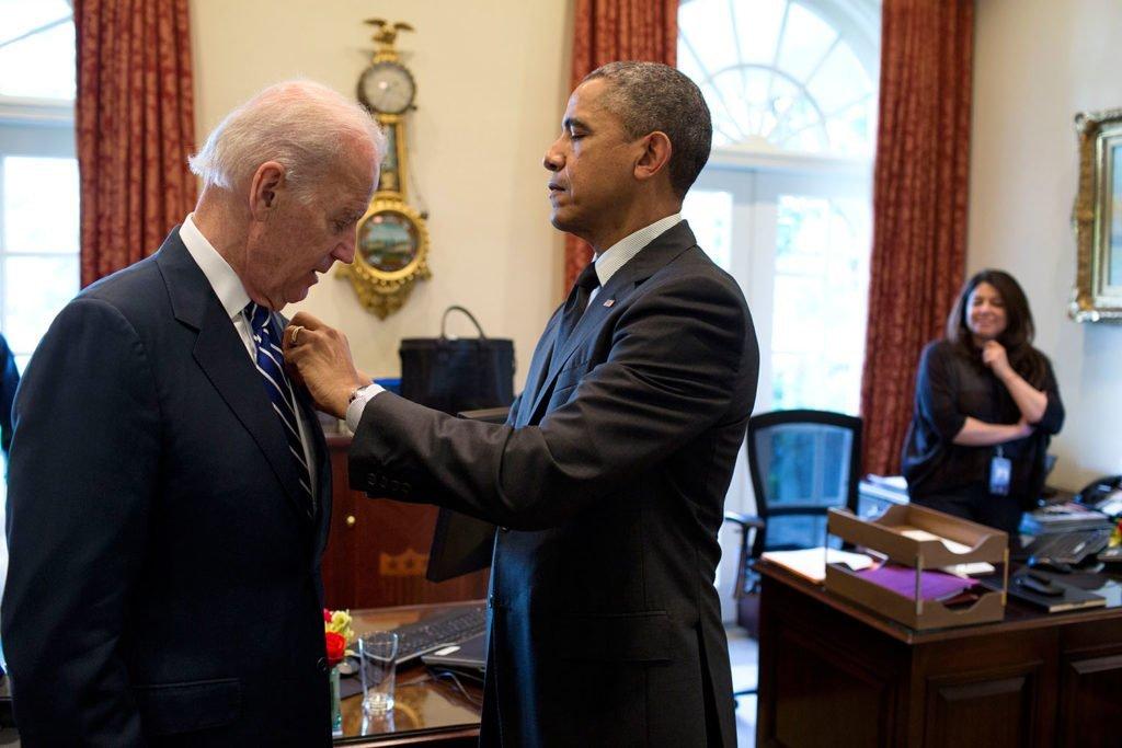 الرئيس السابق أوباما يعدّل ضبط الدبوس الخاص بنائبه وقتها جو بايدن في البيت الأبيض، 23 مايو 2014